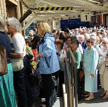 Singers queue in the sunshine outside the RAH